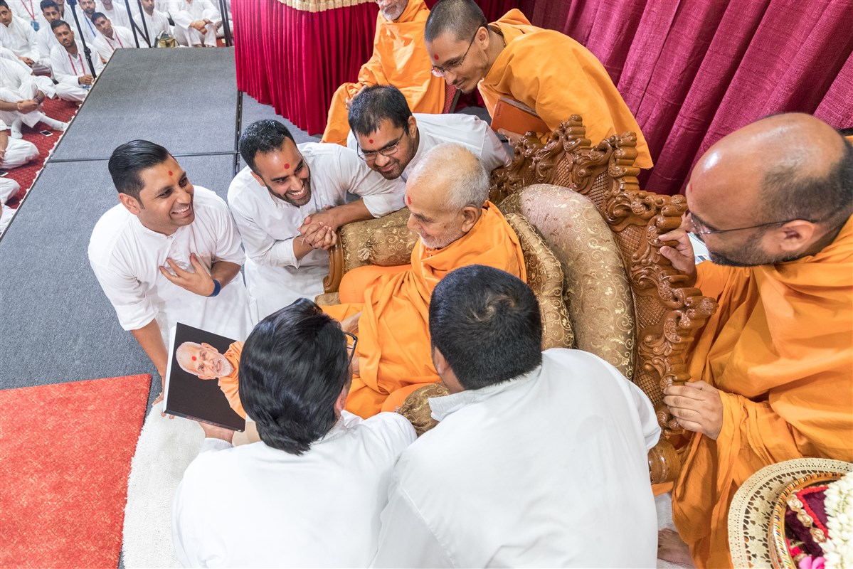 Youths present a pictorial book depicting Mahant Swami Maharaj's interactions with his gurus