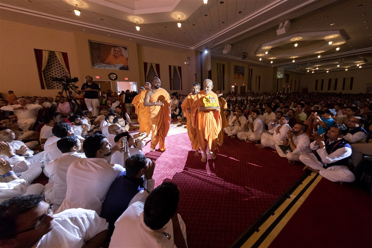 Swamishri enters the Yuvak/Yuvati Din program holding Shri Harikrishna Maharaj