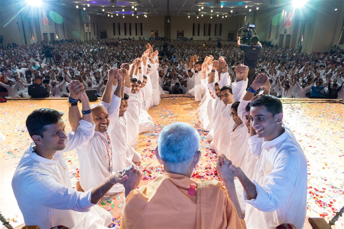 Youths and Swamishri join hands as a gesture of unity