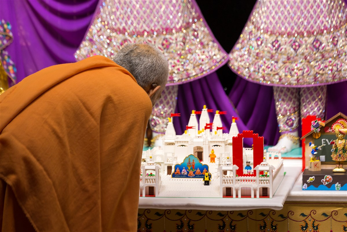 Swamishri engrossed in viewing a model of the Mandir made by a child