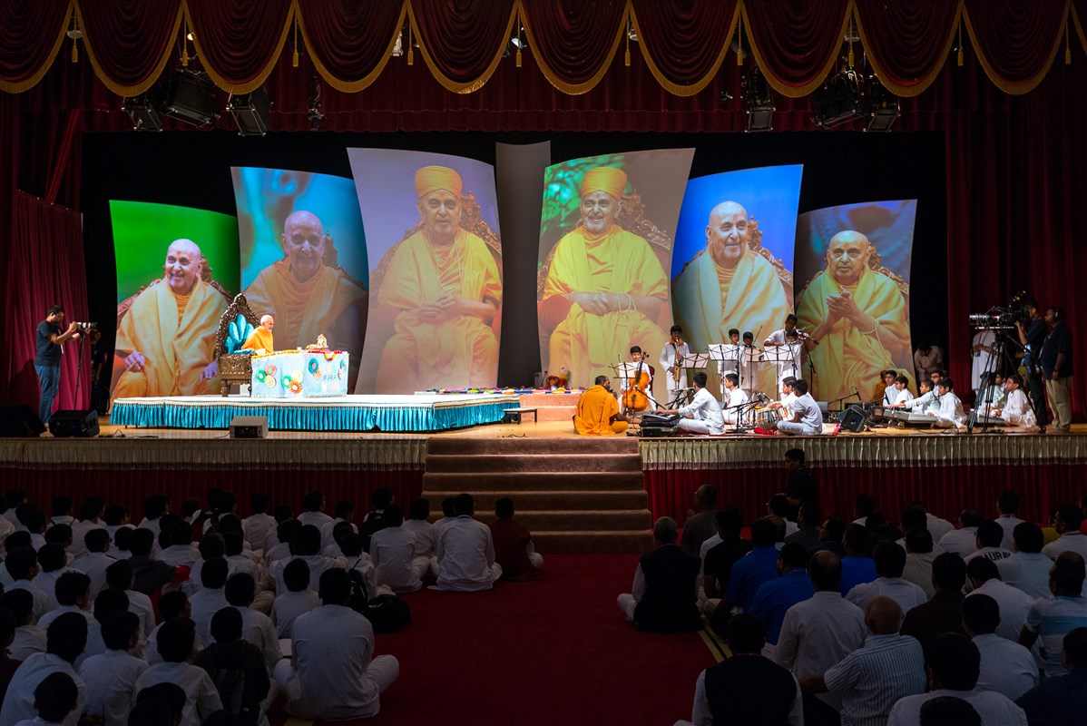 Children sing bhajans and play various instruments during Swamishri's puja