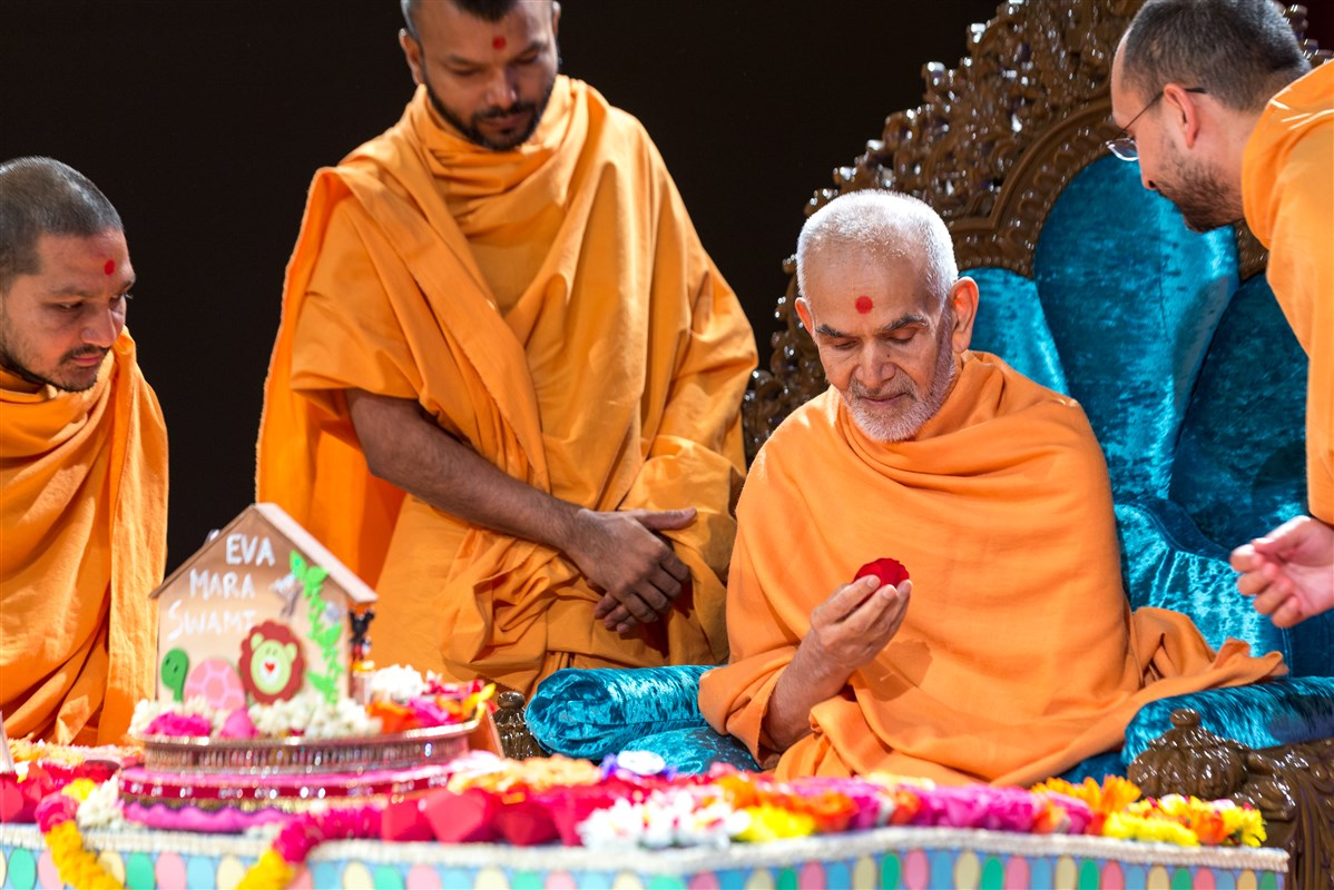 Swamishri reads childrens' prayers written inside decorative paper flowers