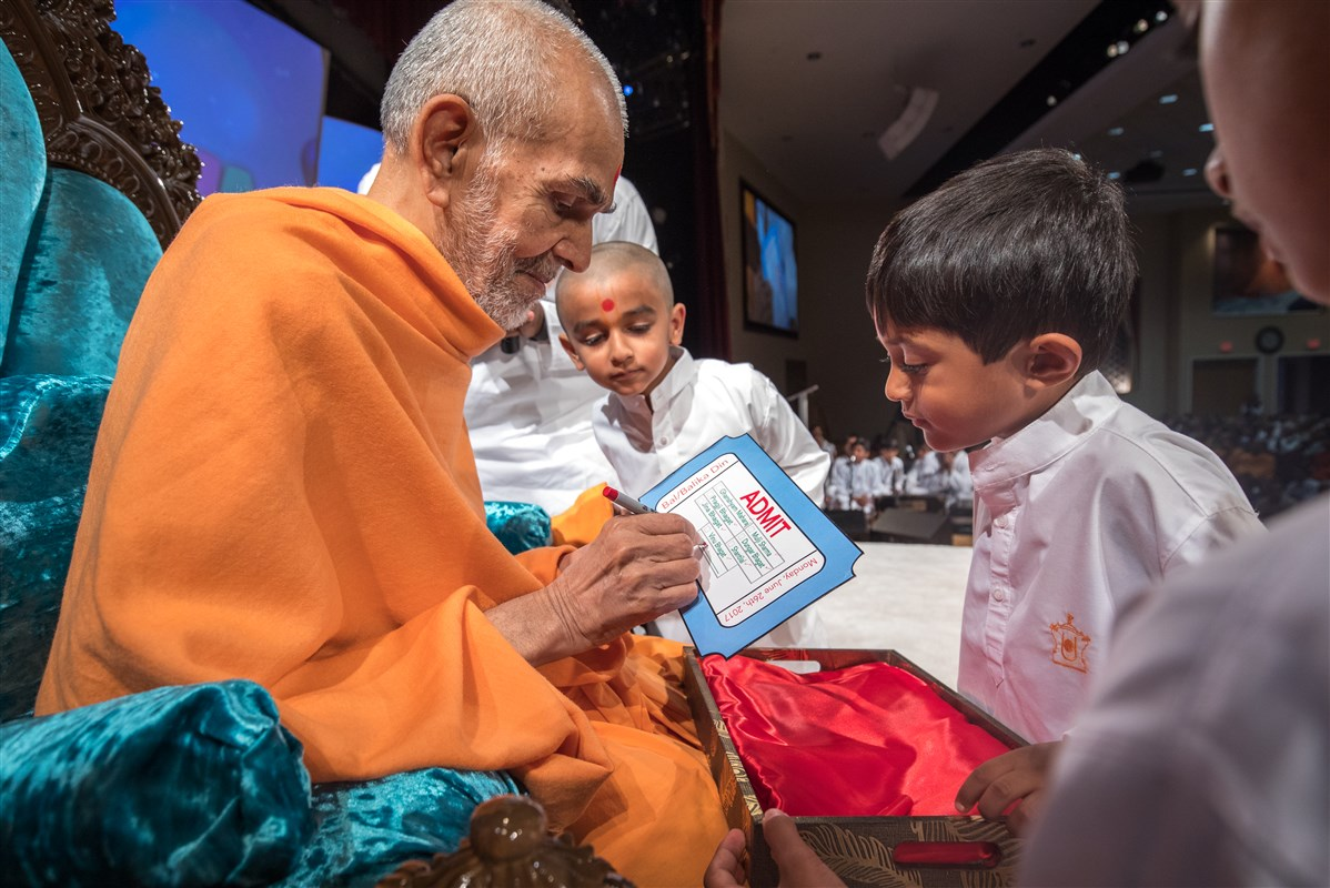 Swamishri signs an invitation from two children saying he will be attending the Bal-Balika Din