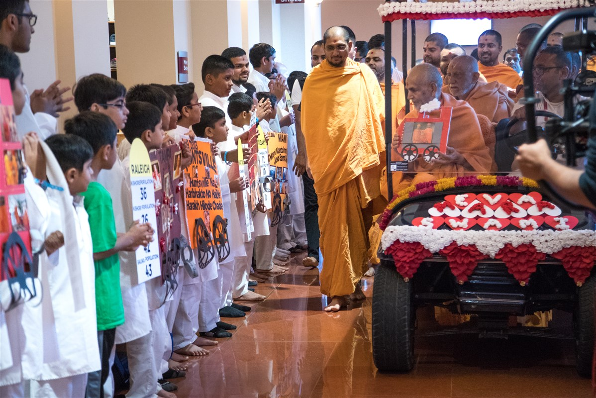 Children from various centers present reports of their activities to Swamishri