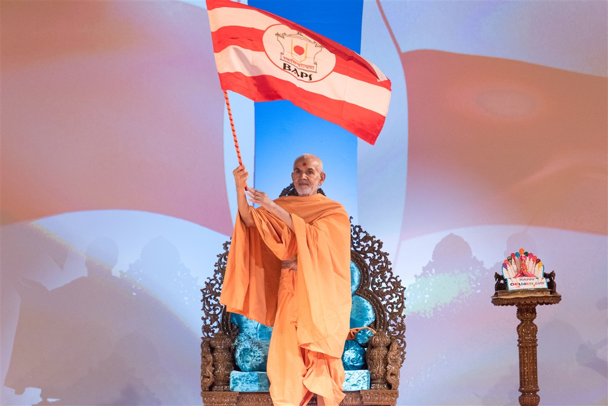 Swamishri waves the BAPS flag to conclude the assembly