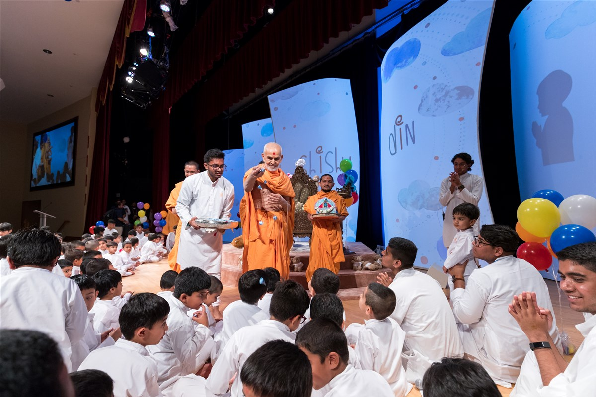 Swamishri gives candy to the children