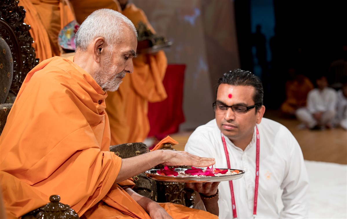 Swamishri sanctifies the janois to be worn by the new initiates taking part in the upanayana sanskar ceremony