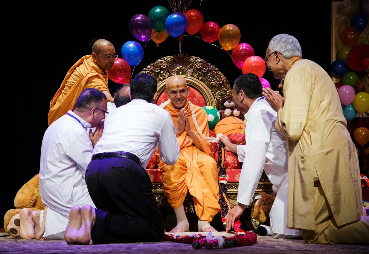 Devotees offer a garland to welcome Swamishri