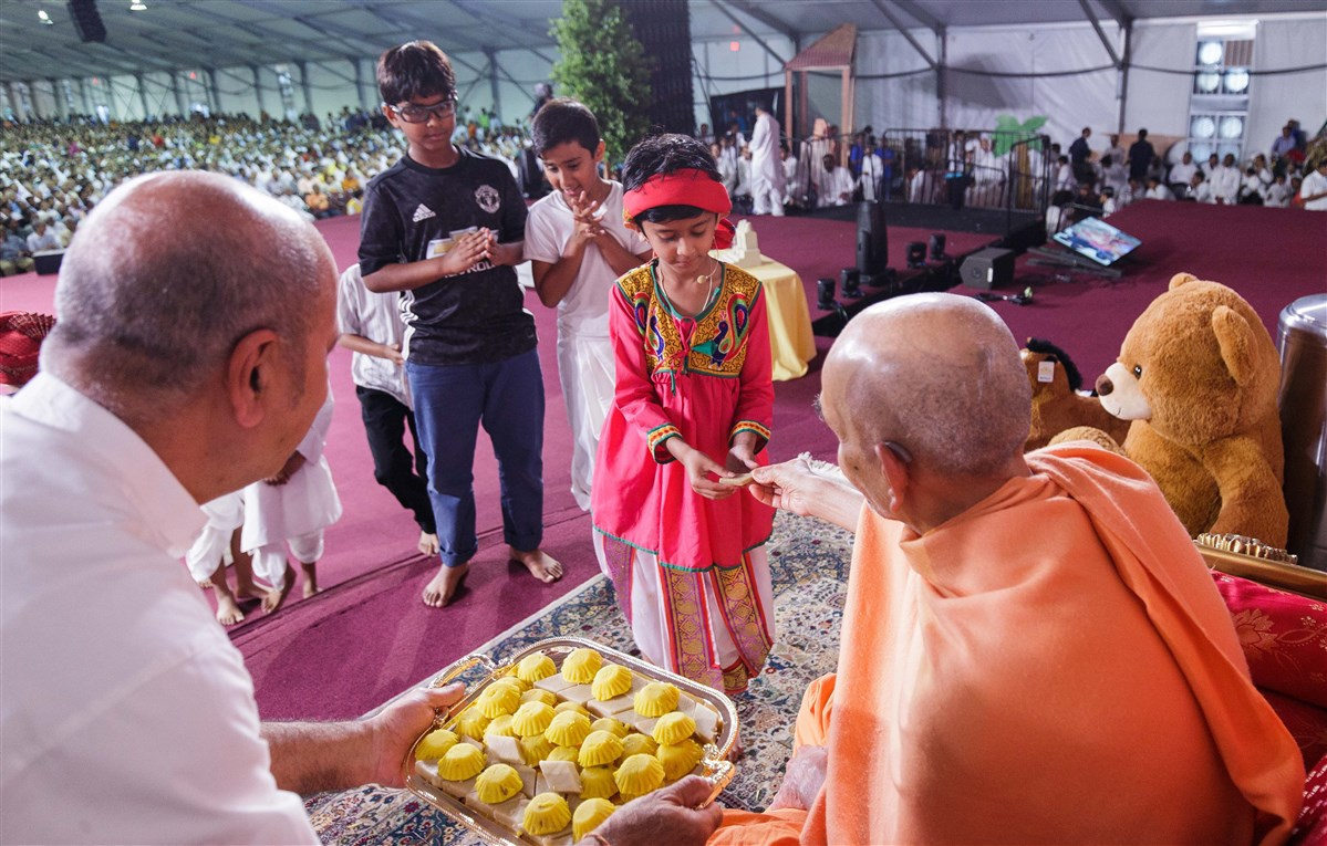 Swamishri offers sweets to children