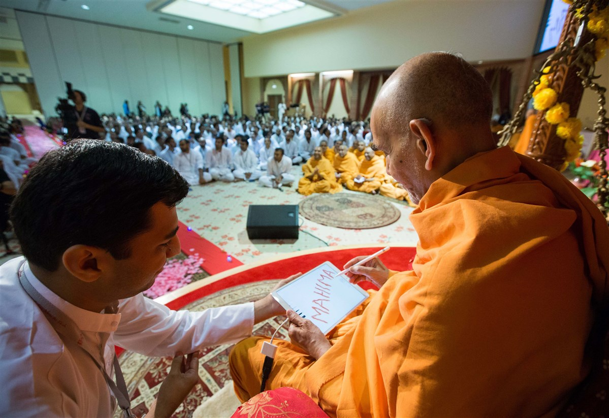 Swamishri delivers a message by writing on a tablet