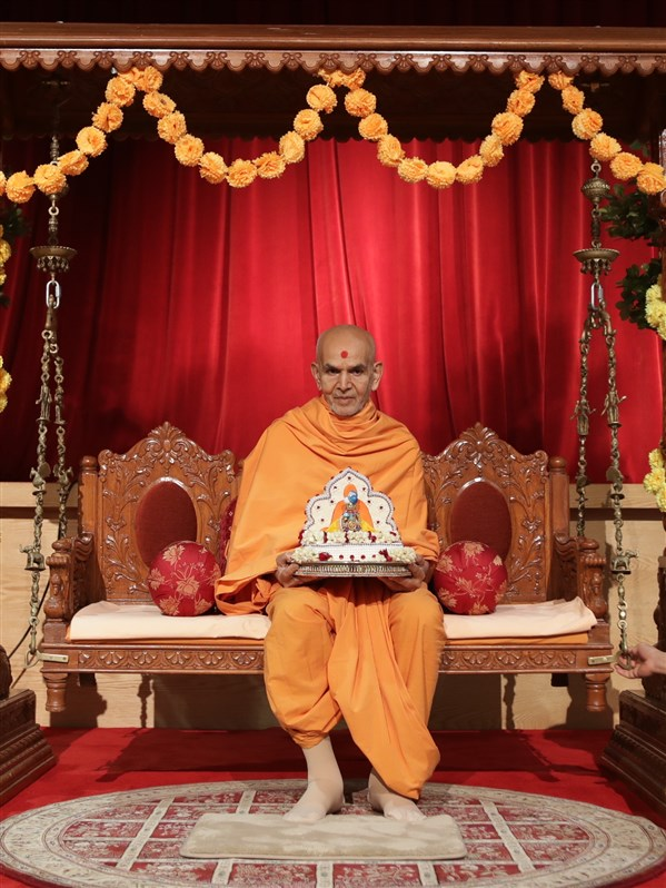 Swamishri seated on a swing with Shri Harikrishna Maharaj