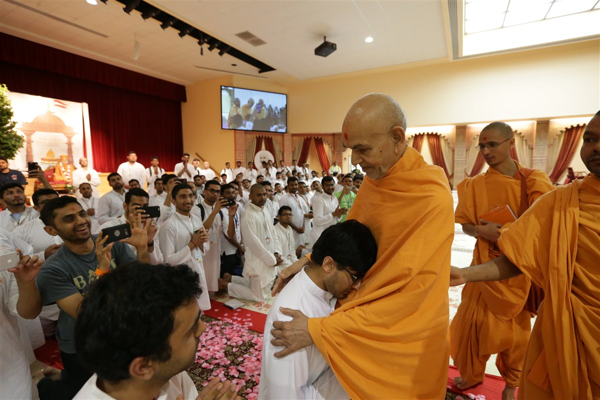 Swamishri embraces a youth