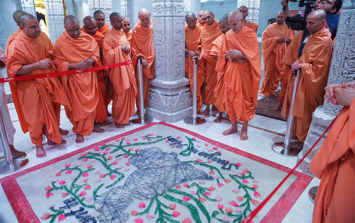 Swamishri views a decorative string art design