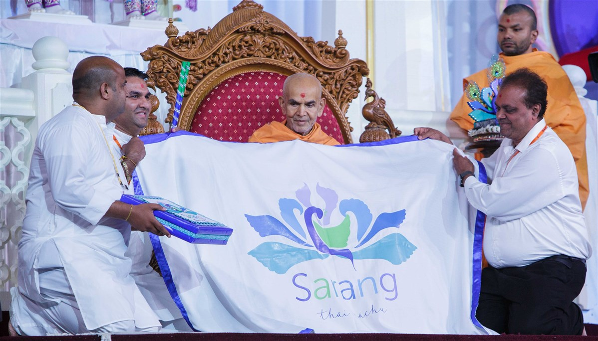 Devotees present Swamishri with a shawl