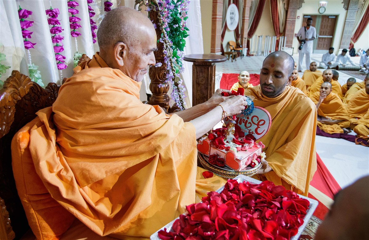 Swamishri showers Shri Harikrishna Maharaj with flower petals