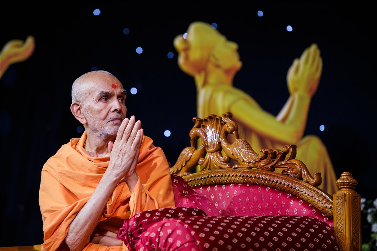 Swamishri folds his hands to devotees in the audience