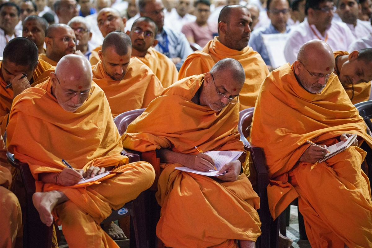 Swamis take notes during Swamishri's discourse