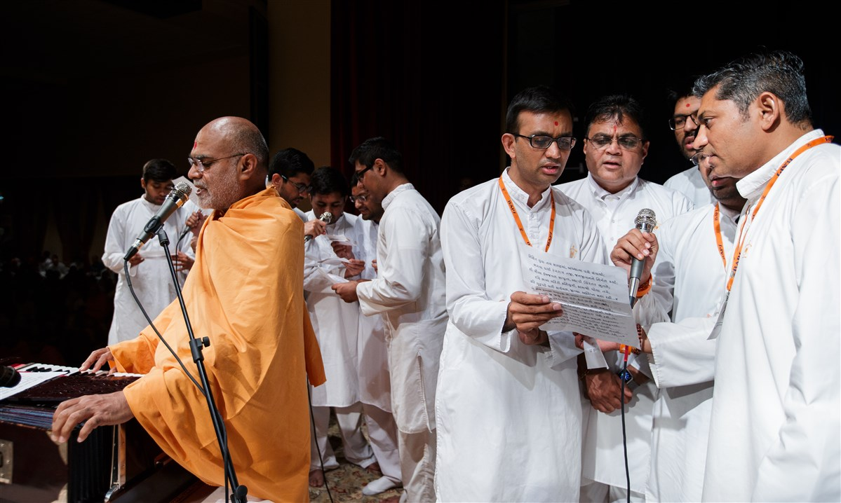 Swamis and devotees sing during Swamishri's puja