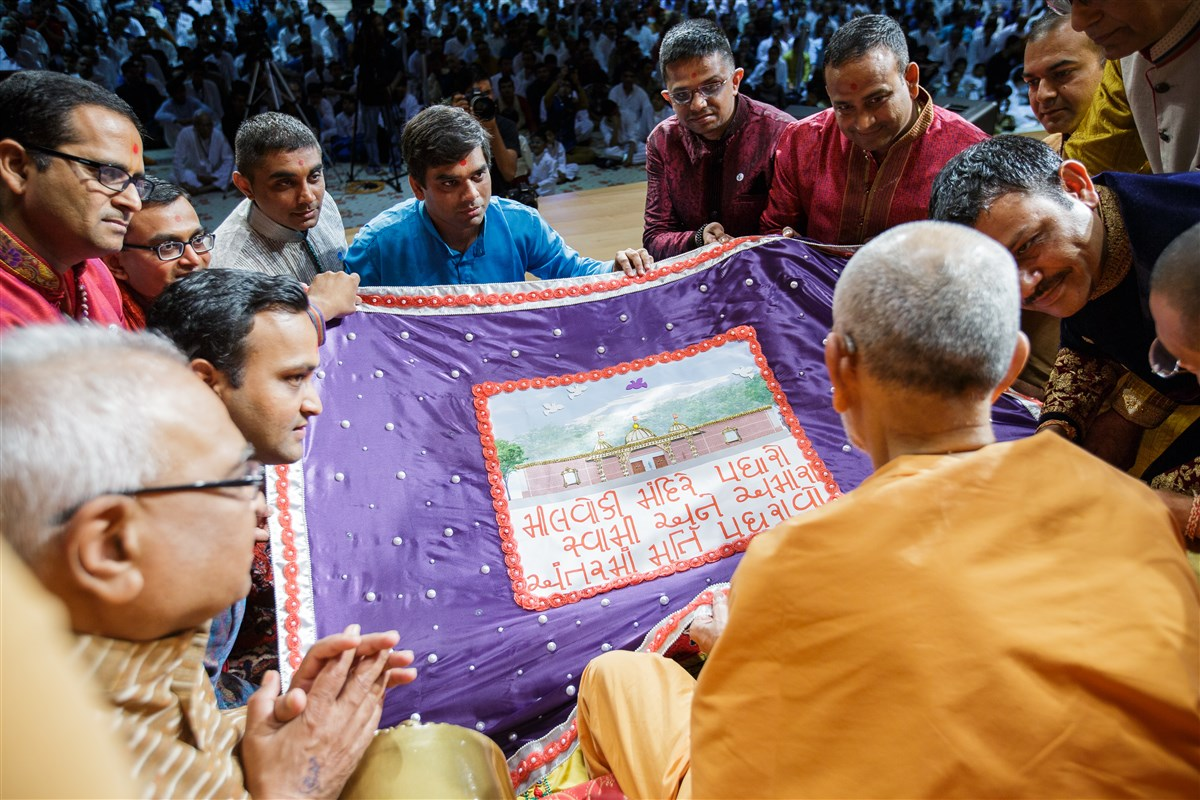 Swamishri is offered a shawl by devotees from Milwaukee