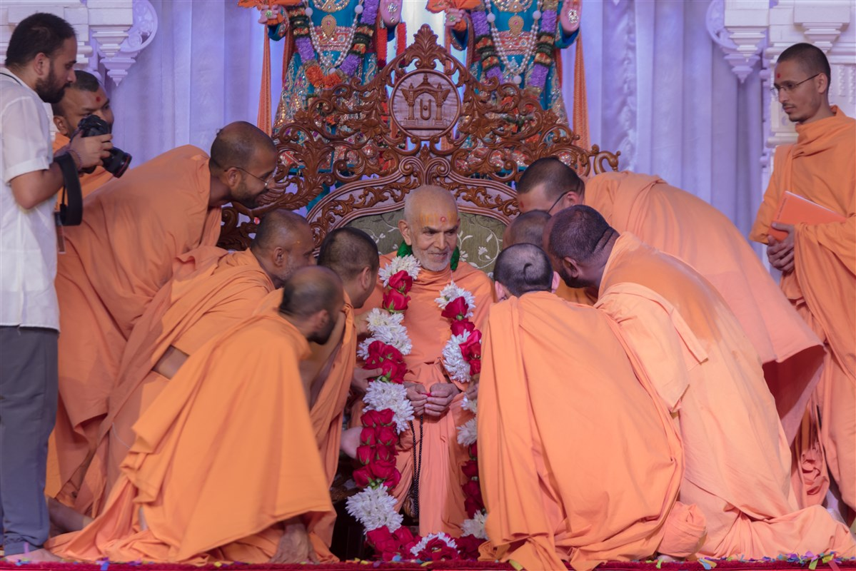 Swamis welcome Swamishri with a garland