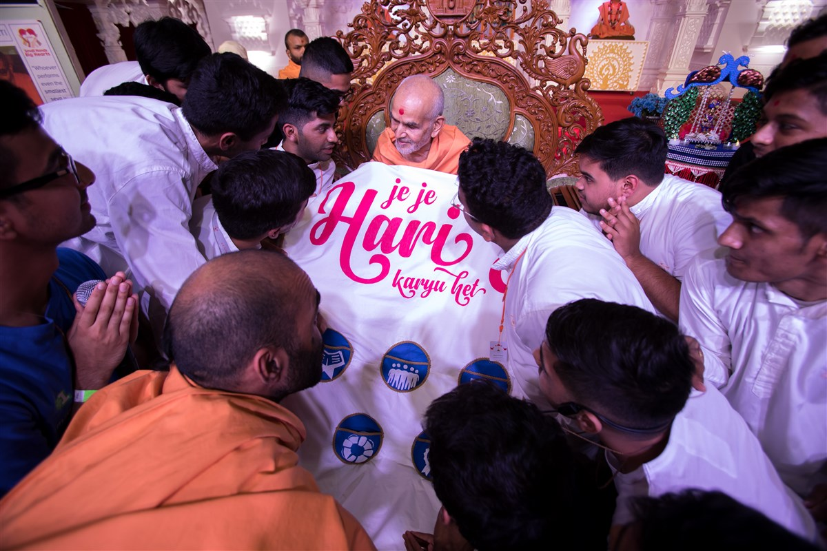 Youths honor Swamishri with a decorative shawl
