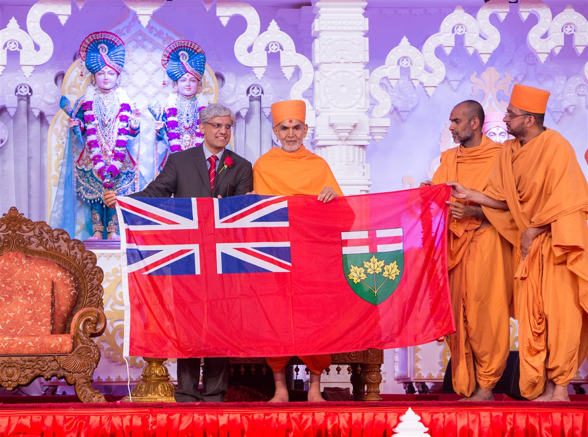 Dr. Shafiq Qaadri, MPP for Etobicoke North, presents Swamishri with a flag of the Province of Ontario