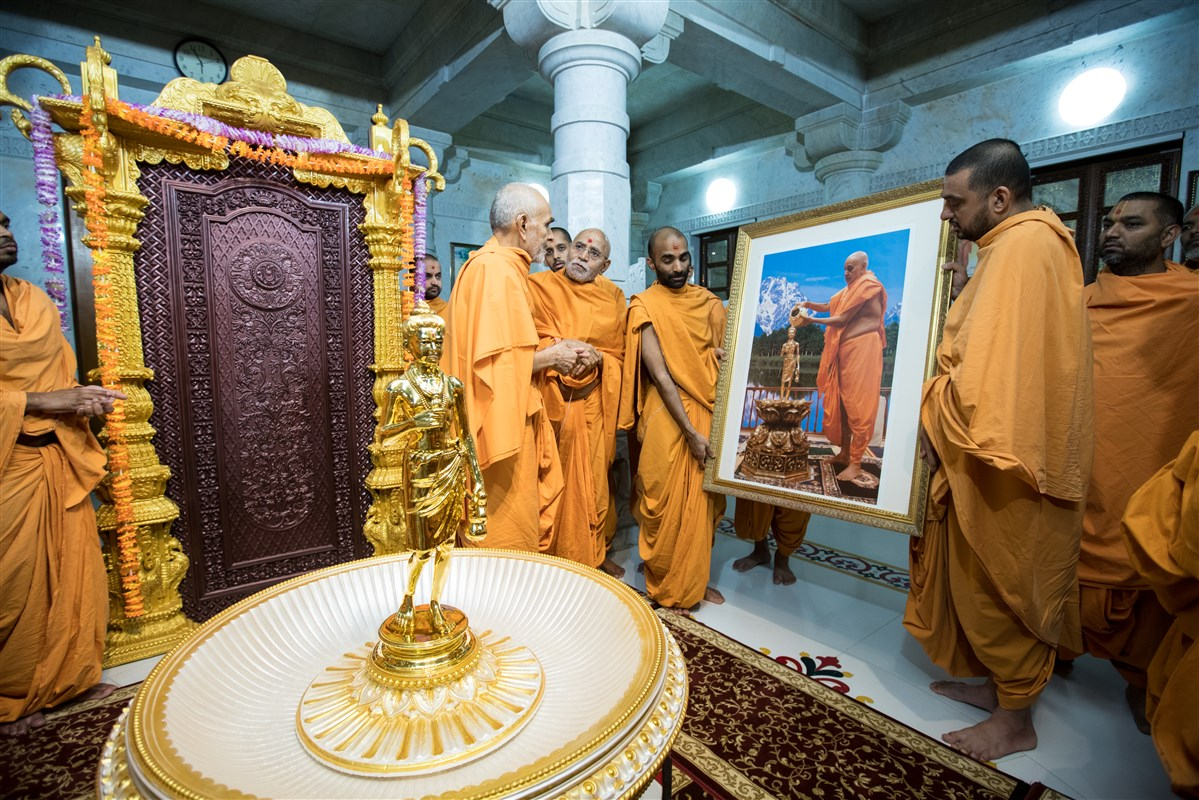 Swamishri engrossed in darshan of a murti of Pramukh Swami Maharaj doing abhishek in Toronto