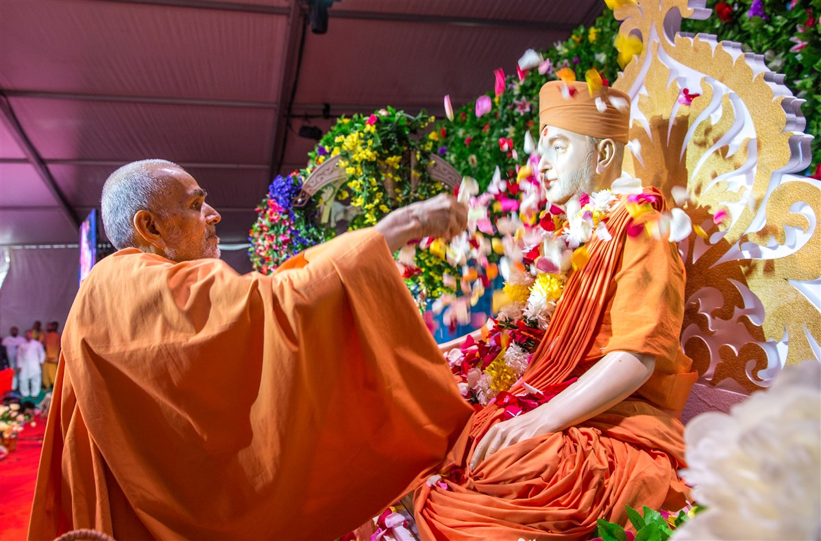 Swamishri offers flowers to Pramukh Swami Maharaj