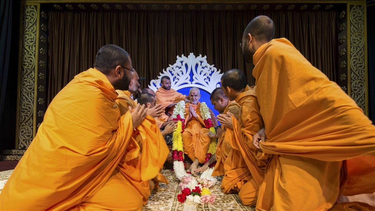 Swamis honor Swamishri with a garland