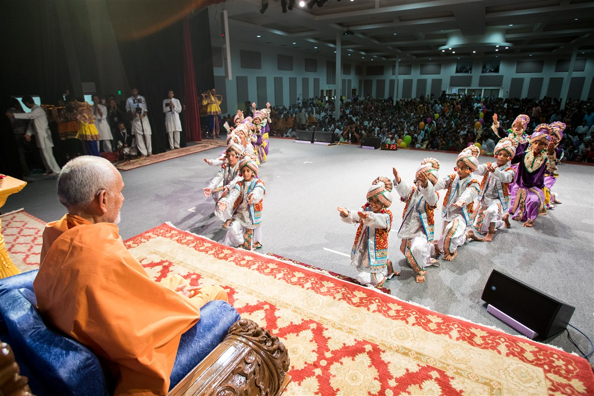 Children perform a welcome dance before Swamishri
