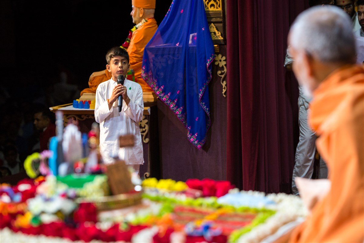 A child recites shlokas before Swamishri during his morning puja