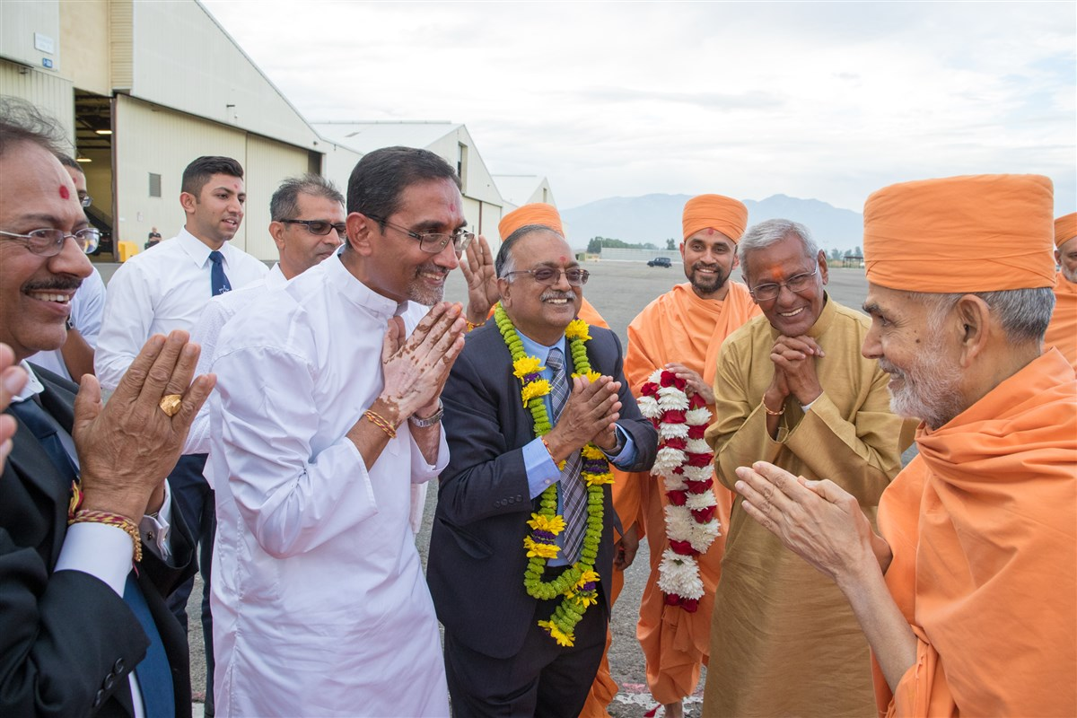 Param Pujya Mahant Swami Maharaj arrives in Los Angeles and greets devotees with folded hands