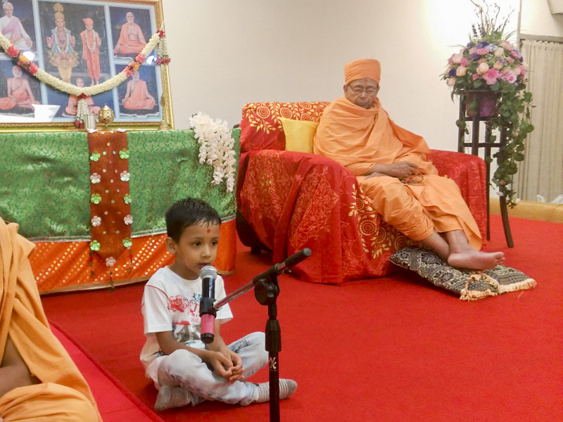 A child sings kirtan during the assembly