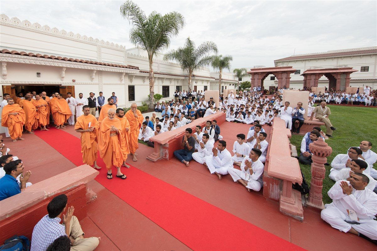 Param Pujya Mahant Swami Maharaj greets devotees with folded hands