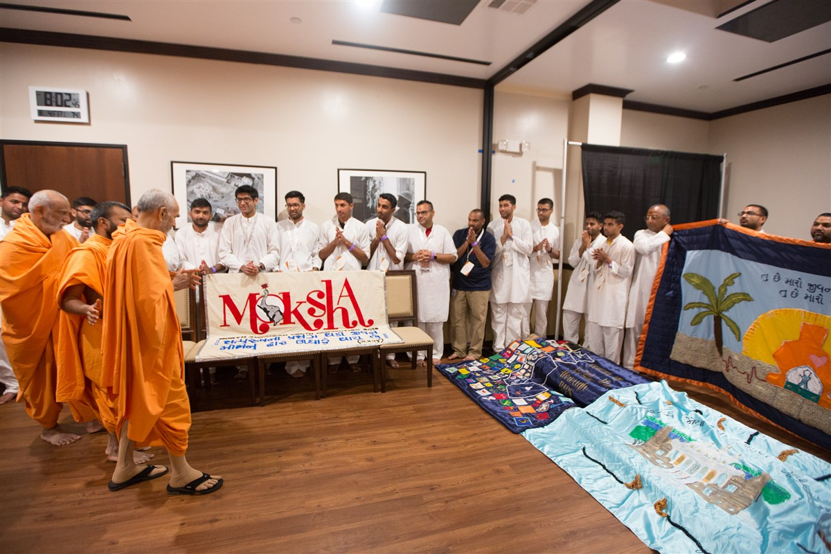 Youths present Swamishri with various decorative shawls