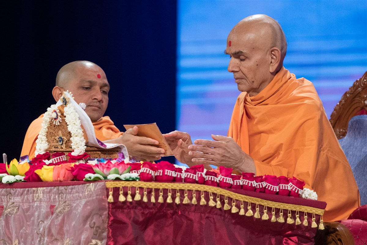 Swamishri touches the feet of the murti of Shri Akshar Purushottam Maharaj
