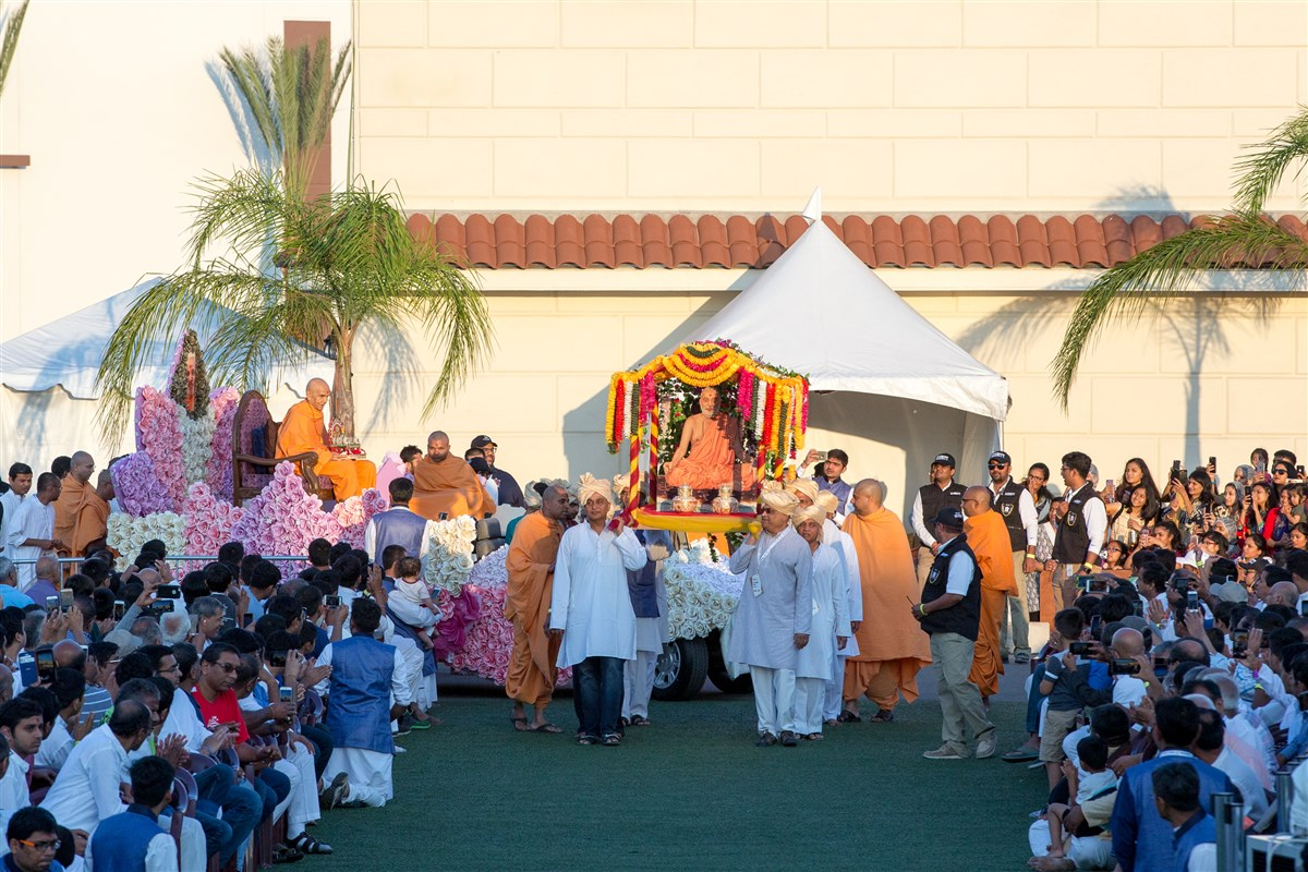 Swamishri arrives to the evening assembly on a rath