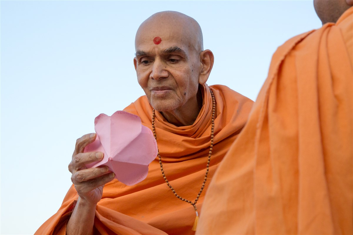 Swamishri reads the Swaminarayan Mantra written on decorative flower petals