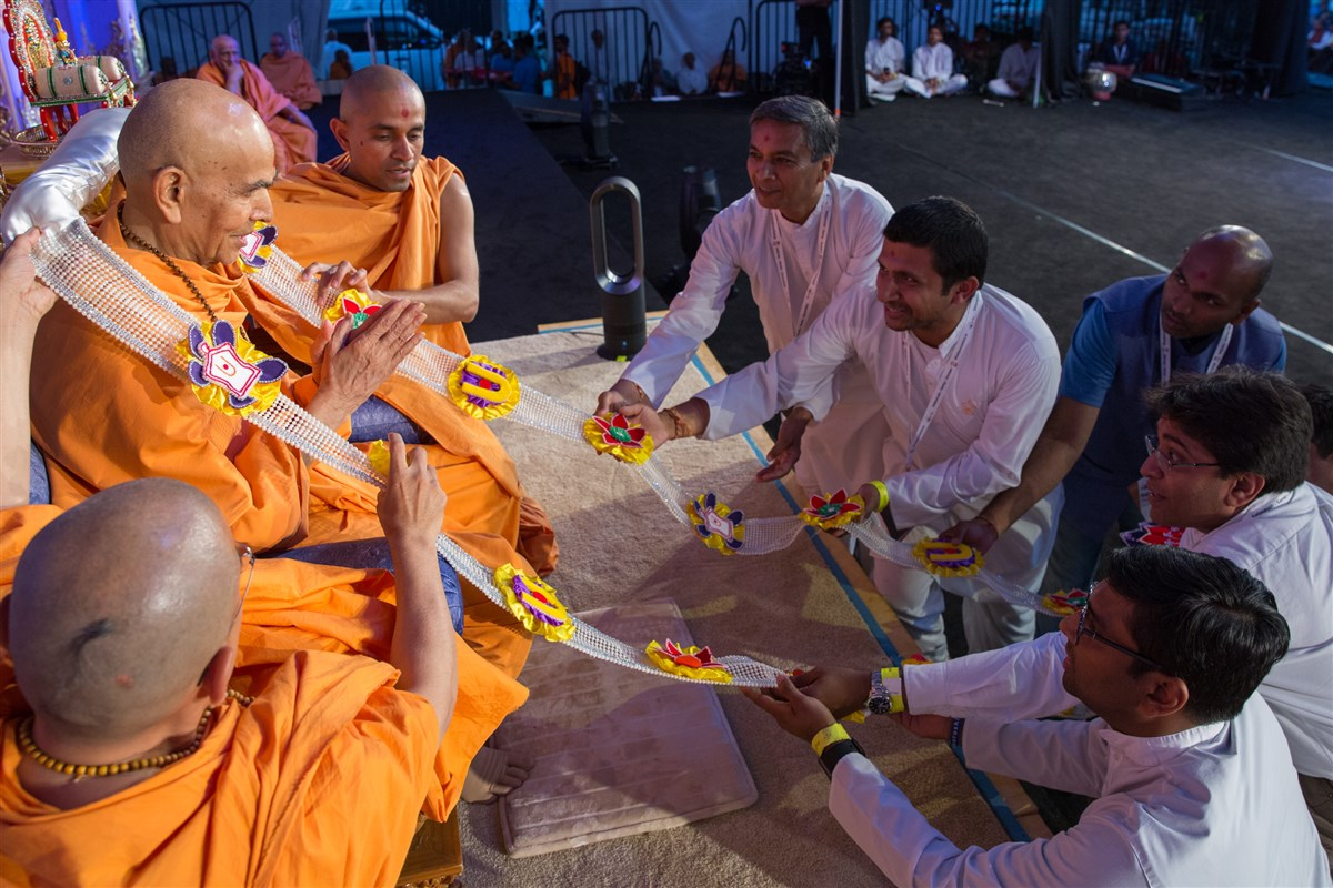 Devotees offer Swamishri a garland