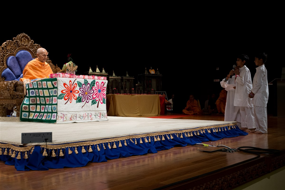 Children recite shlokas before Swamishri during his puja