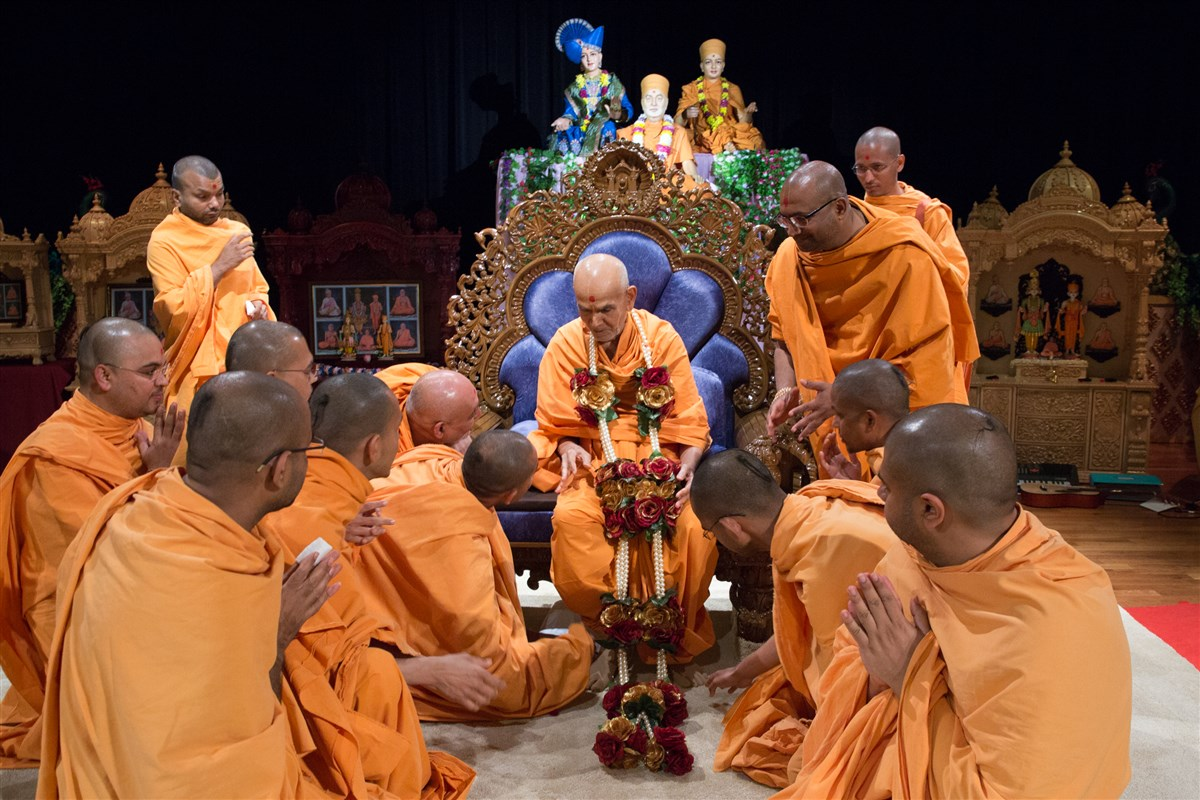 Swamis offer Swamishri a garland