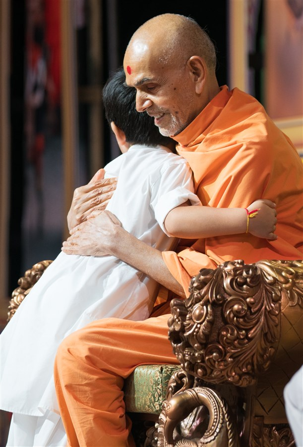 Swamishri embraces a child
