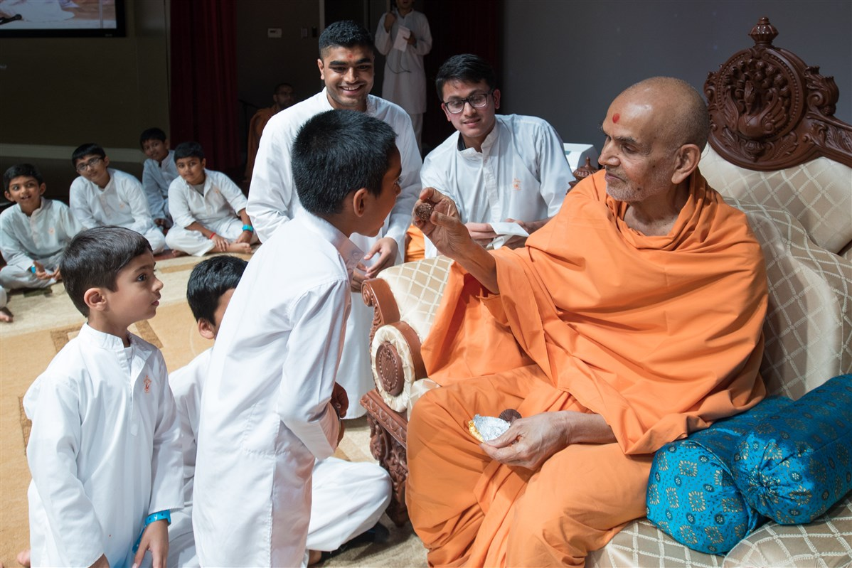 Swamishri feeds a child