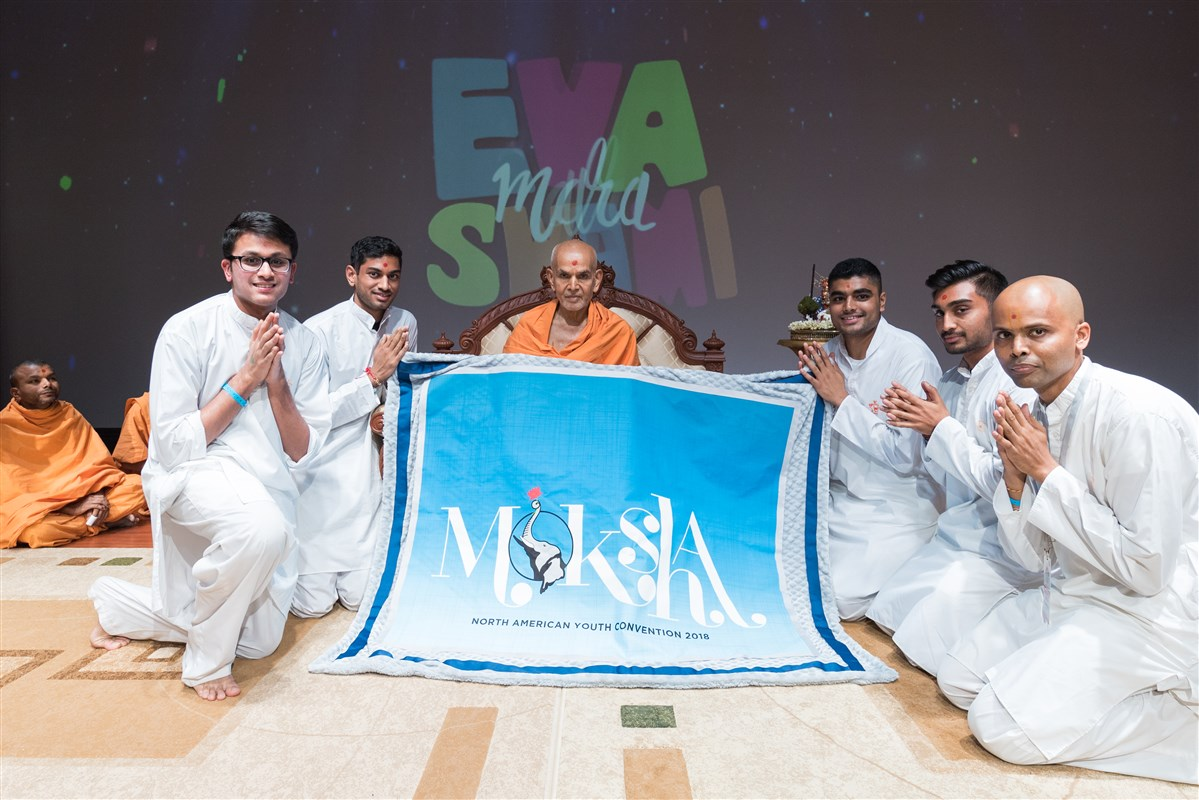 Youths offer Swamishri a shawl with the North American Youth Convention 2018  theme 'Moksha'