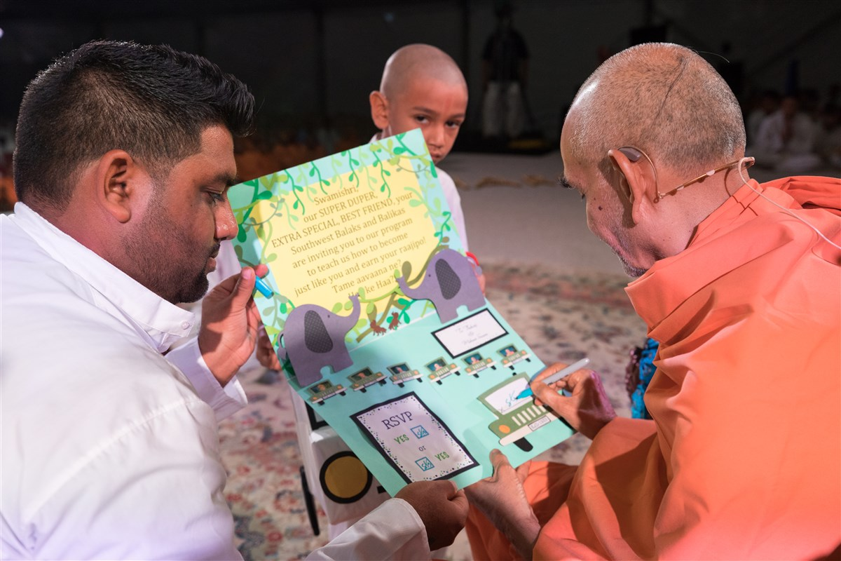 Swamishri signs an invitation to attend the Bal-Balika Din