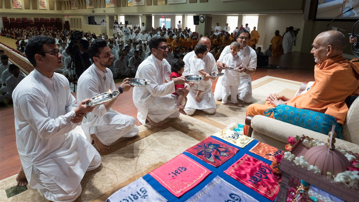 Youths welcome Swamishri to the assembly by performing arti