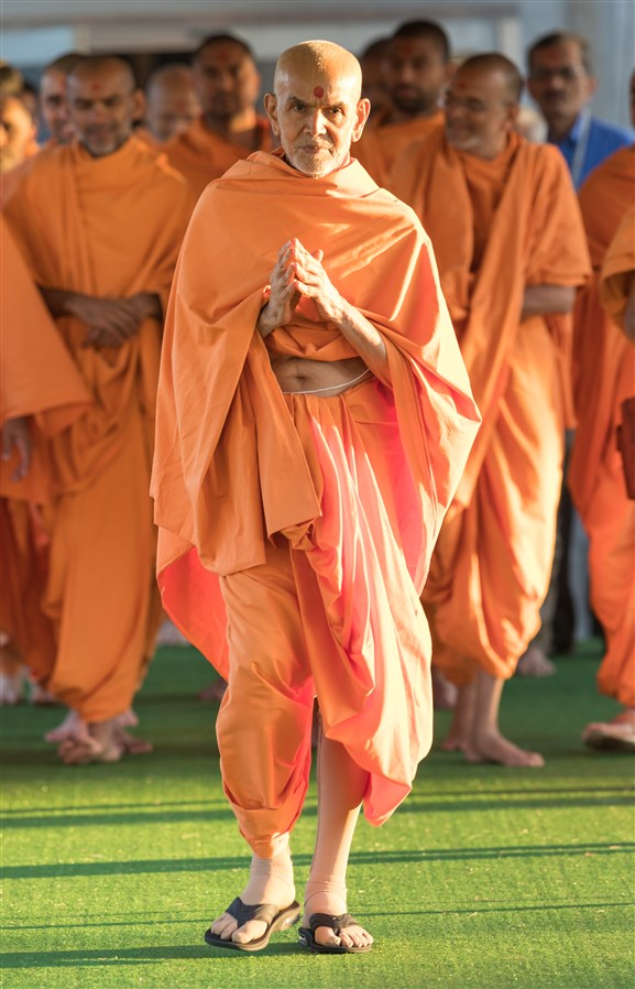 Swamishri walks after puja with folded hands