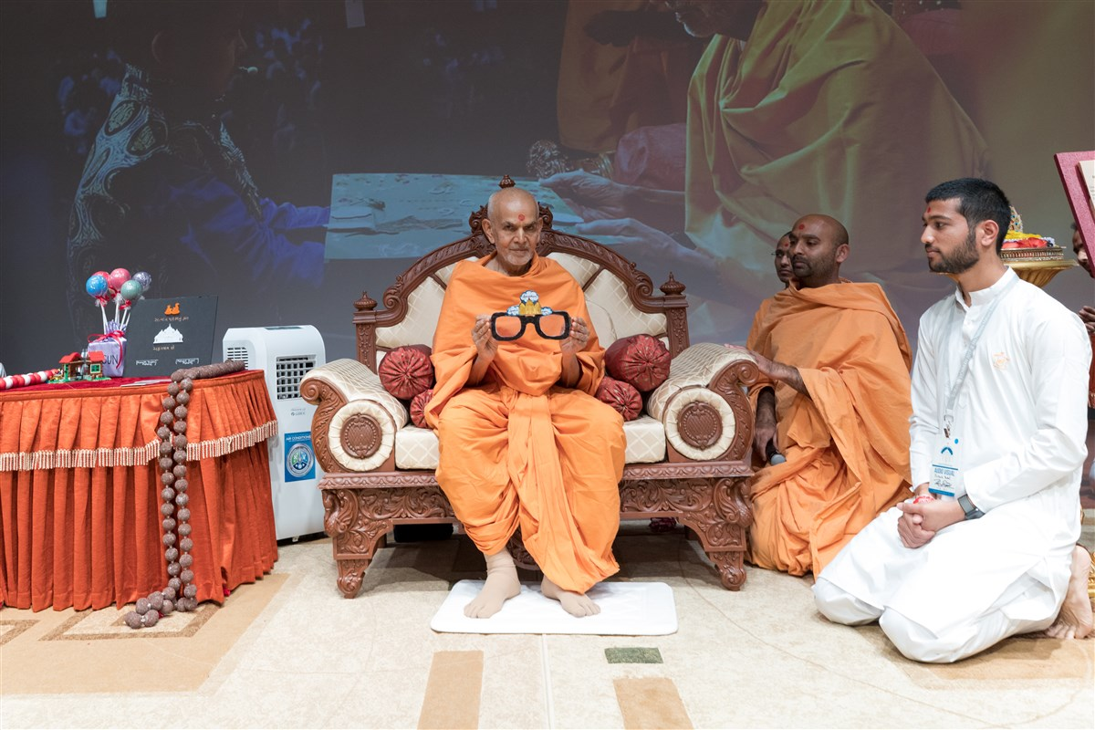Swamishri uses glasses to demonstrate to the assembly to see divyabhav in all