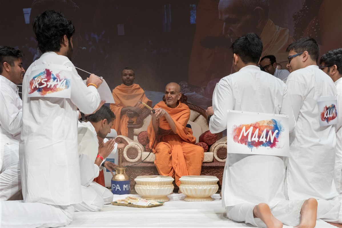 Swamishri sprays youths representing various swabhavs with saffron colored water