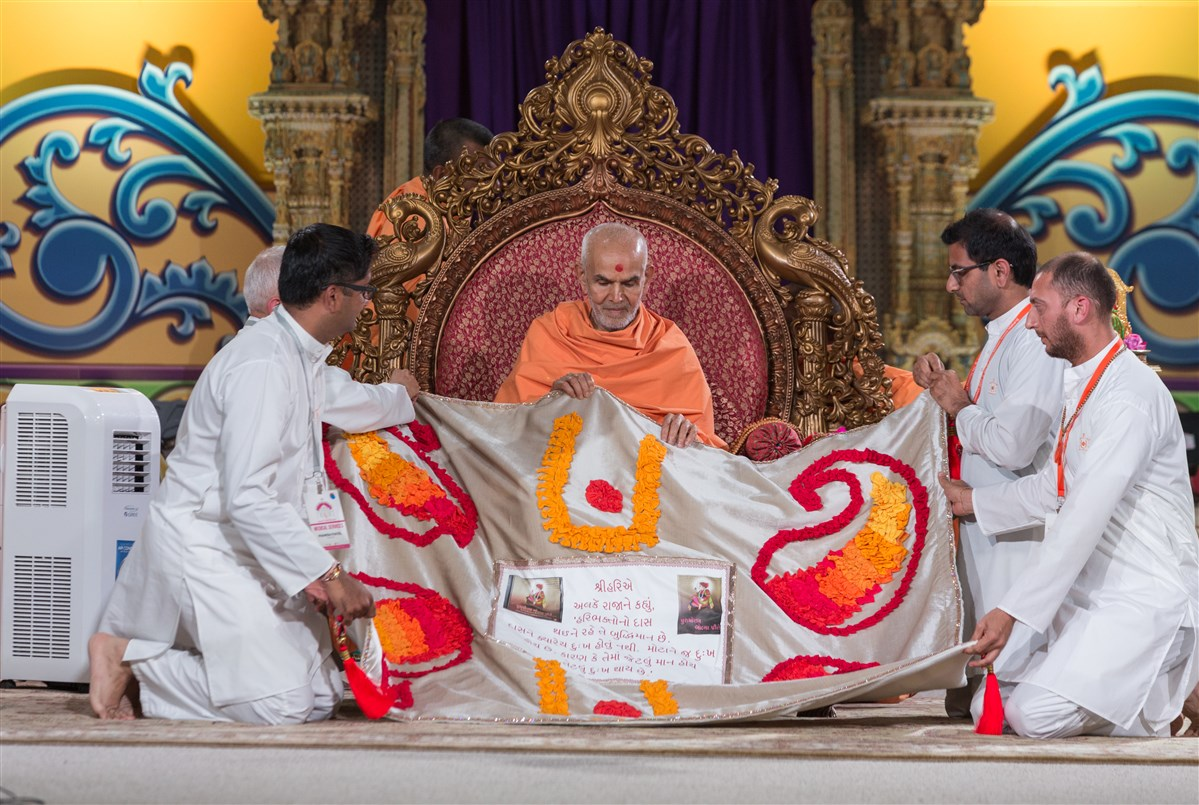 Swamishri is offered a shawl by devotees